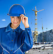 Builder Pretty Girl At Helmet On A Building Background stock photo