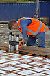 Builder Ties Off The Reinforcing Before Concrete Is Poured Into The Foundations Of A Large Building stock image