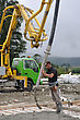 Builder Uses A Concrete Pump To Direct Wet Concrete Into The Foundations Of A Large Building