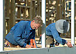 Builder Using Nail Gun On Building Site While Colleague Measures Up stock image