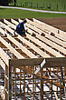 Builder Working On First Floor Framework On Building stock photo