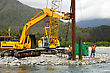 Builders Drive Pylons For A Concrete Bridge Over A Small River In Westland, New Zealand