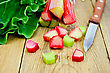 Bundle Of Stalks Of Rhubarb, Cut Pieces Of Rhubarb With A Leaf And A Knife On A Wooden Board stock photography