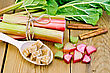 Bundle Of Stalks Rhubarb, Cut Pieces Of Rhubarb With A Sheet And A Knife, A Spoon Of Sugar Cubes, Cinnamon On A Wooden Board stock image