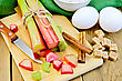 Bundle Of Stalks Rhubarb, Cut Pieces Of Rhubarb, Knife, Sugar Cubes, Cinnamon, Two Eggs, Flour, Napkin On Wooden Board stock photo