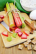 Bundle Of Stalks Rhubarb, Cut Pieces Of Rhubarb, Knife, Sugar Cubes, Cinnamon, Eggs, Flour, Cloth On A Wooden Board stock image