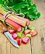 Bundle Of Stalks Rhubarb, Leaf And Cut Pieces Of Rhubarb, A Knife On A Wooden Board stock image