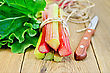 Bundle Of Stalks Of Rhubarb With Leaf, A Knife And A Coil Of Rope On A Wooden Board stock photo