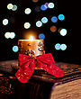Burning Candle And Seasonal Decorations On Bokeh Lights Background