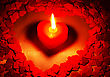 Burning Heart Shaped Candle Over Red Background