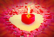 Burning Red Heart Shaped Candle Over Blurry Colorful Background