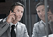 Business Man On Cell Phone Reflected In Glass stock photography