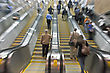 Business People Rushing On The Escalator In Motion Blur
