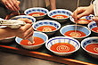 Busy Cooks Garnish Bowls Of Tomato Soup With Fresh Cream stock photography