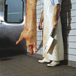 Butcher Holding Cleaver Standing Next To Pig Carcass stock photo