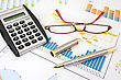 Calculator, Pen And Glasses On Business Charts stock photography