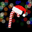 Candy Cane And Hat Of Santa Claus 0n Dark Blurred Background