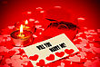 Card With Marriage Proposal And Two Rings And Two Candles Over Red Background stock photo
