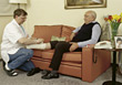 Caretaker Wrapping Senior's Leg stock photography