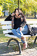 Charming Young Woman Sitting On A Bench In Autumn Park