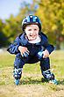 Cheerful Little Boy Riding On Roller Skates Squatting