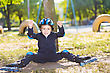 Cheerful Skater Boy In Helmet Sitting Under The Tree stock image