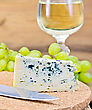 Triangle Cheese With Fungus, Grapes, Wine Glass, Knife On Background Wooden Plank stock photo