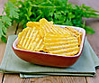 Chips Grooved In A Clay Bowl On A Napkin, Parsley On A Wooden Boards Background stock image