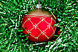 Christmas Red Ball With Golden Patterns On A Background Of Green Tinsel stock photography