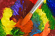 Worn Close Up Of Paintbrush On Colorful Painted Paper stock photography