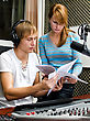 Colleagues Examine Broadcast List In Studio stock photo