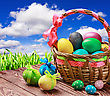 Colored Eggs In The Basket On The Table On A Background Of Blue Sky