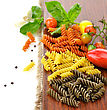 Colorful Pasta On A Cutting Board With Tomatoes And Spices