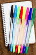 Colorful Pens And Spiral Notebook On The Wooden Desk