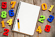 Colorful Plastic Numbers And Empty Notebook With Pencil stock photography