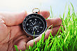 Navigation Compass In Hand On A Background Of Green Grass stock photo