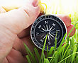 Navigation Compass In Hand On A Background Of Green Grass stock image