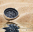 Compass In The Sand By The Water stock photo