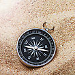 Navigation Compass In The Sand Lit By The Rays Of The Sun stock photography