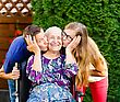 Contented Grandmother Being Loved And Kissed By Beautiful Grandchildren stock photography