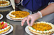 Cook Placing Cream On The Top Of A Passionfruit Cheesecake stock photo