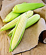 Corn On The Cob On Burlap On Wooden Board Backgrounds stock photo