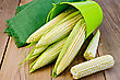 Corn On The Cob With Green Bucket And Napkin On The Background Of Wooden Boards stock photo