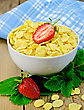 Cornflakes In A White Bowl With Half A Strawberry, Leaves And Berries Of A Strawberry, A Napkin On A Wooden Boards Background