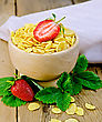 Cornflakes In Wooden Bowl, Strawberry Leaves And Berries, A Napkin On A Wooden Boards Background stock photo