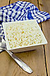 Cottage Cheese In A White Square Bowl, A Blue Checkered Napkin, Spoon On A Background Of Wooden Boards