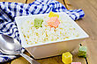Cottage Cheese In A White Square Bowl With Colored Sugar Cubes, Blue Checkered Napkin, Spoon On A Wooden Board
