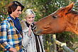 Couple And A Horse Asking For Caress stock photography