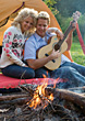 Couple Camping & Playing Guitar By A Campfire stock photography