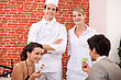 Couple Dining At Restaurant, A Cook And A Waitress Behind Them stock photography